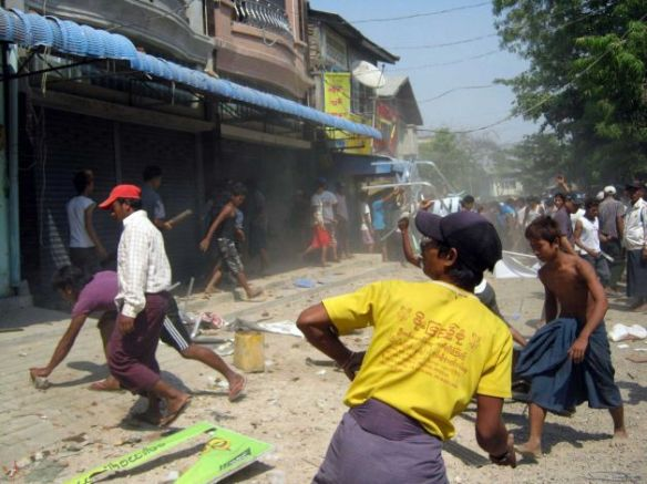 In this Thursday, March. 21, 2013 photo, a group of people try to destroy a building in Meikhtila, Mandalay division (AP Photo)
