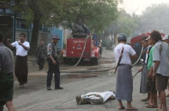 A policeman and residents stand around the body of a man in a street in riot-hit Meiktila, central Myanmar on March 22, 2013. STR/AFP/Getty Images)