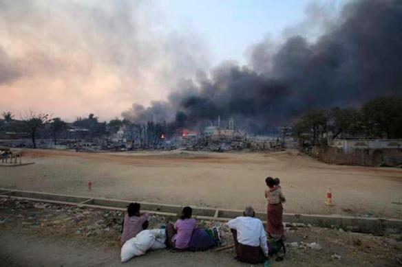People look on as smoke rises over a Meikhtila neighborhood on Thursday. (Photo: Reuters / Soe Zeya Tun)