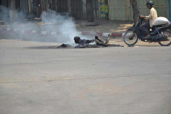 A smoldering charred body lies in the middle of a road in Meikhtila. (Photo: Teza Hlaing / The Irrawaddy )