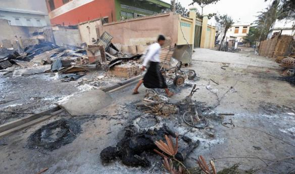 A resident walks past a burnt body in riot-hit Meiktila, central Myanmar on March 21, 2013. AFP PHOTO/ Soe Than WIN