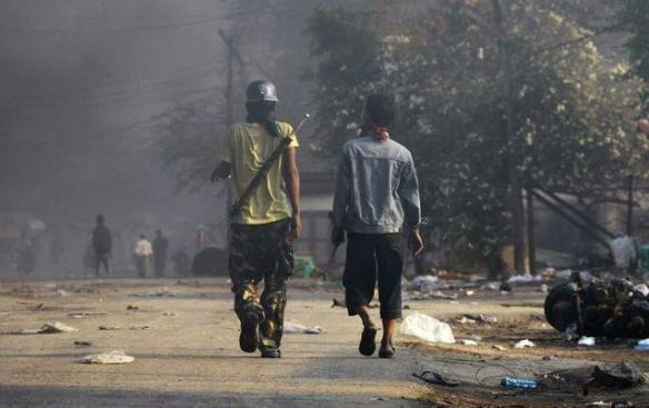 MEIKHTILA BURNS: People carry weapons during riots in Meikhtila on Friday. Unrest in central Myanmar has stoked fears that last year's sectarian bloodshed is spreading into the country's heartland. Picture: REUTERS